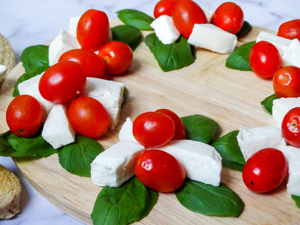 close up of Caprese Christmas Wreath on a round wooden board, made with basil leaves, fresh mozzarella cubes and grape tomatoes