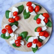 Caprese Christmas Wreath on a round wooden board, made with basil leaves, fresh mozzarella cubes and grape tomatoes