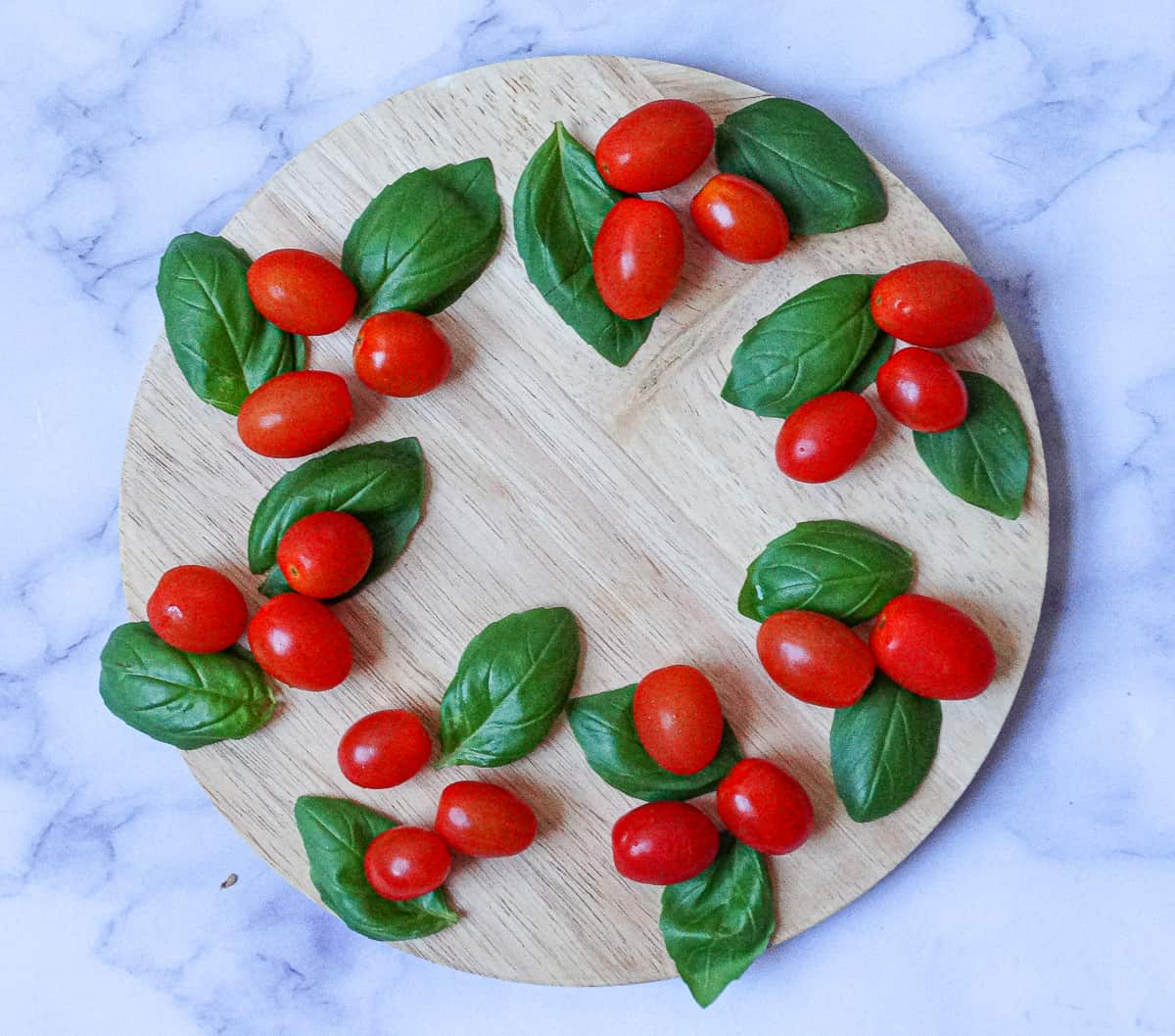 basil leaves and grape tomatoes spread out on a round wooden board
