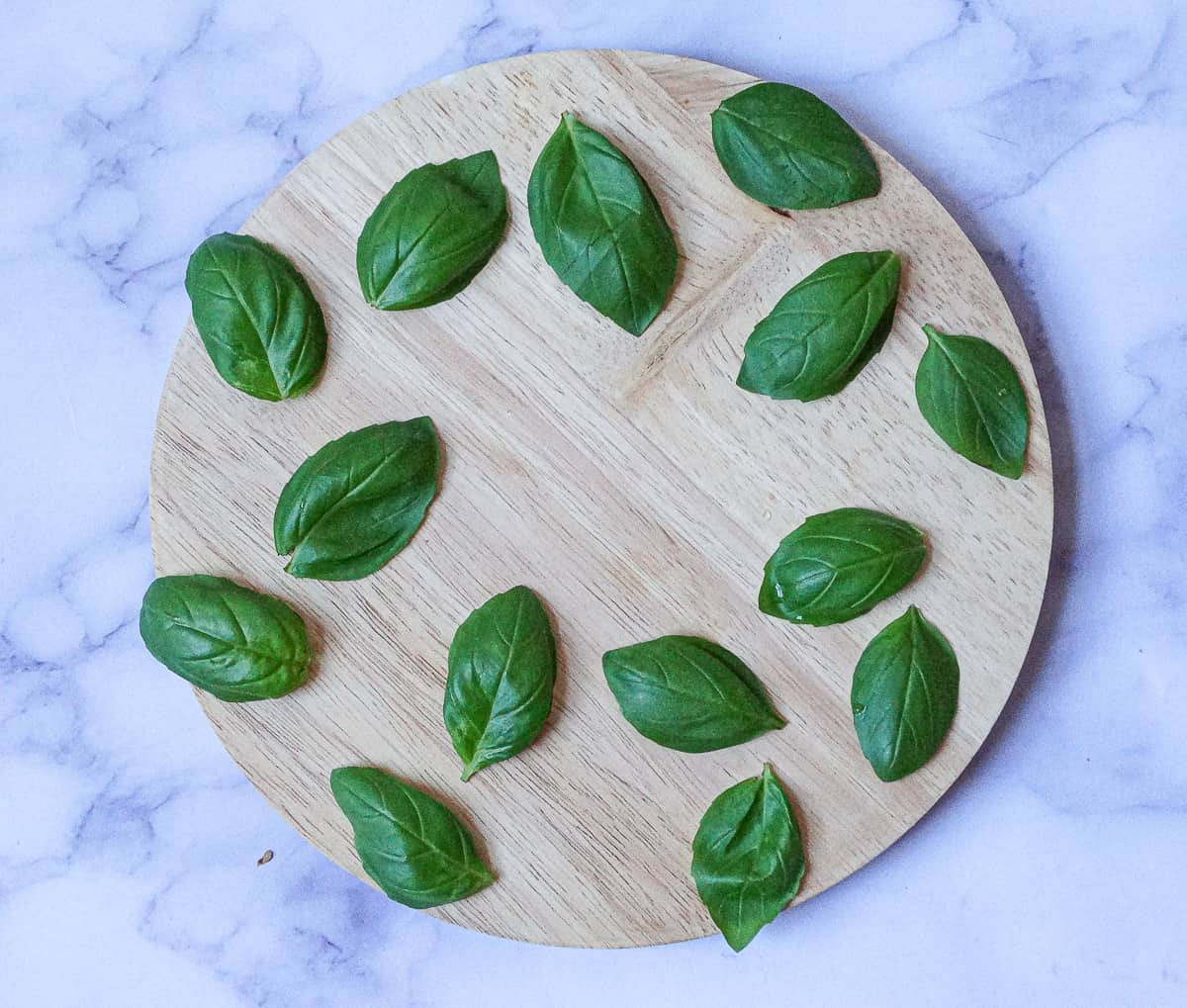 basil leaves spread out on a round wooden board