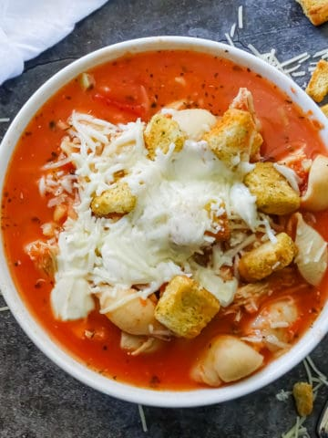 easy chicken parmesan crockpot soup in a white bowl topped with croutons, melted shredded parmesan and fresh mozzarella