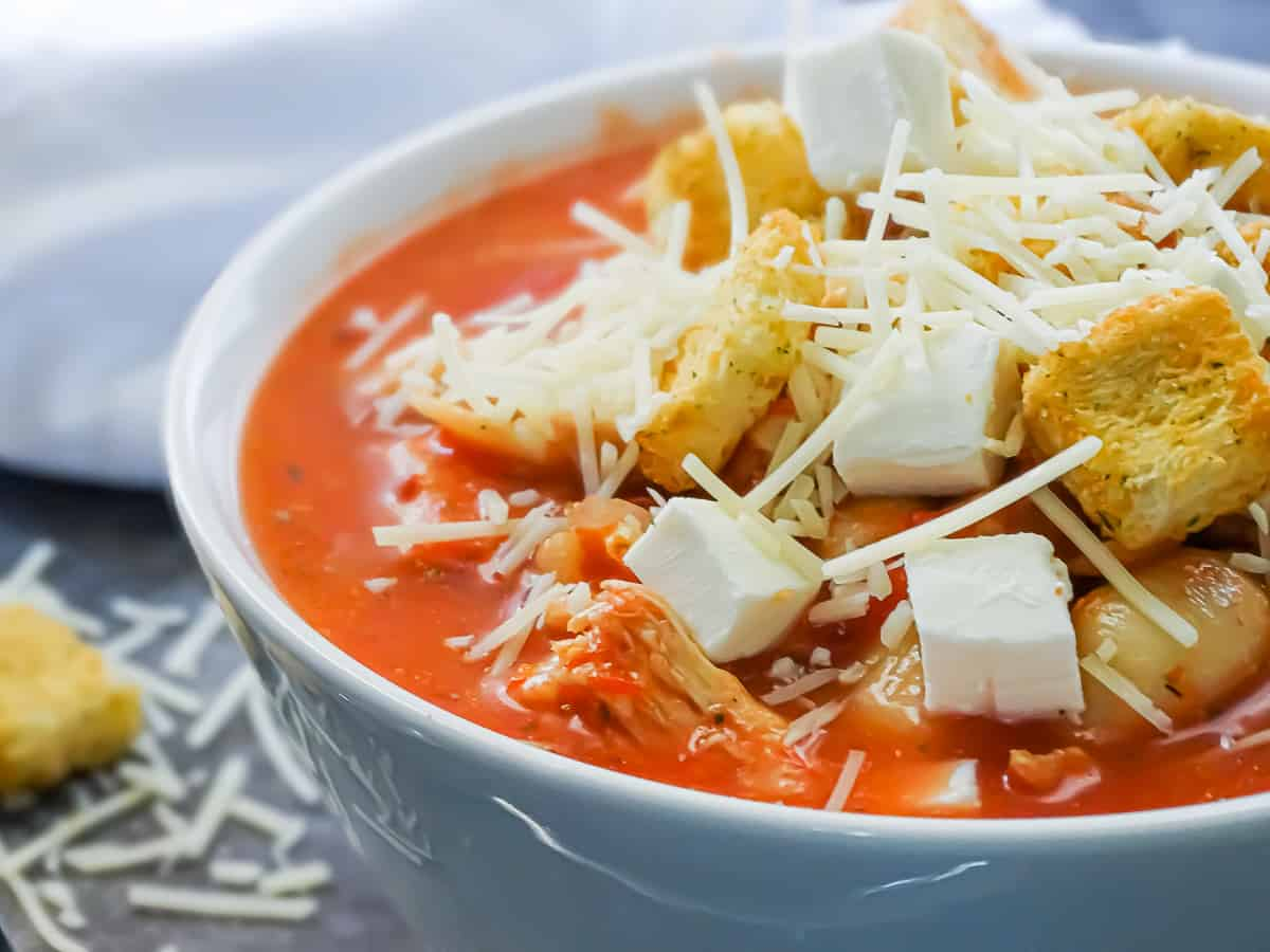 easy chicken parmesan crockpot soup in a white bowl topped with croutons, shredded parmesan and fresh mozzarella