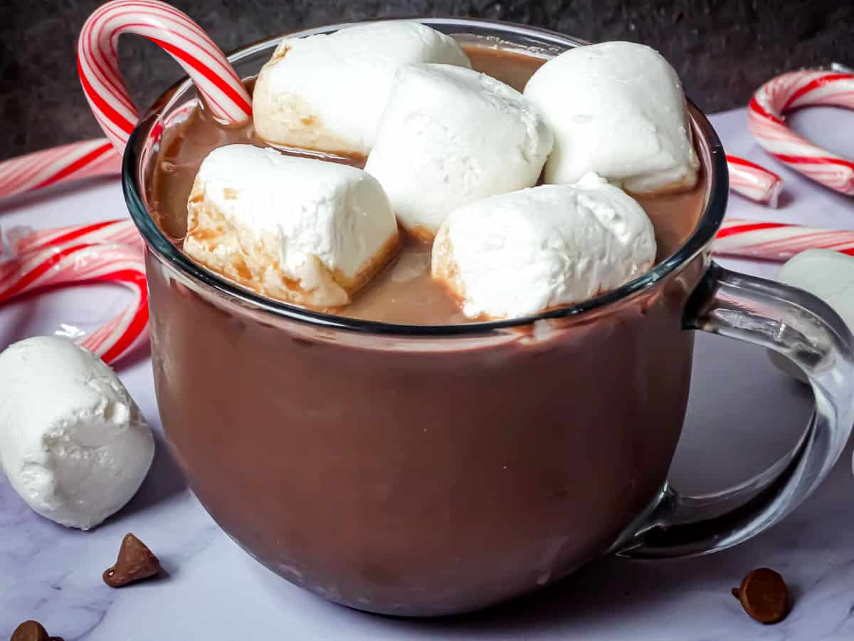 crockpot hot chocolate in a clear mug topped with marshmallows and surrounded by candy canes