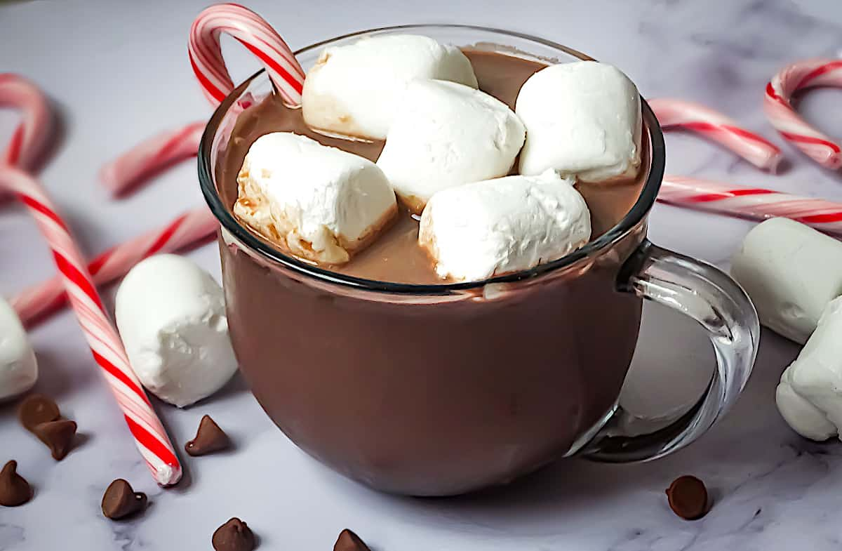 hot chocolate in a clear mug with marshmallows and candy canes