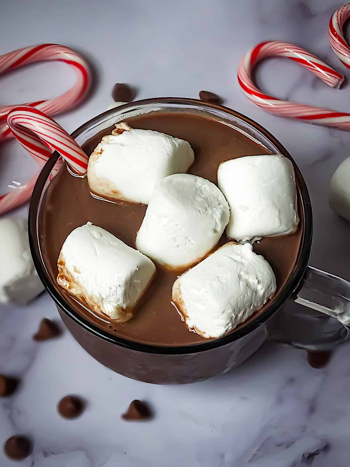 crockpot hot cocoa in a mug with candy canes and marshmallows
