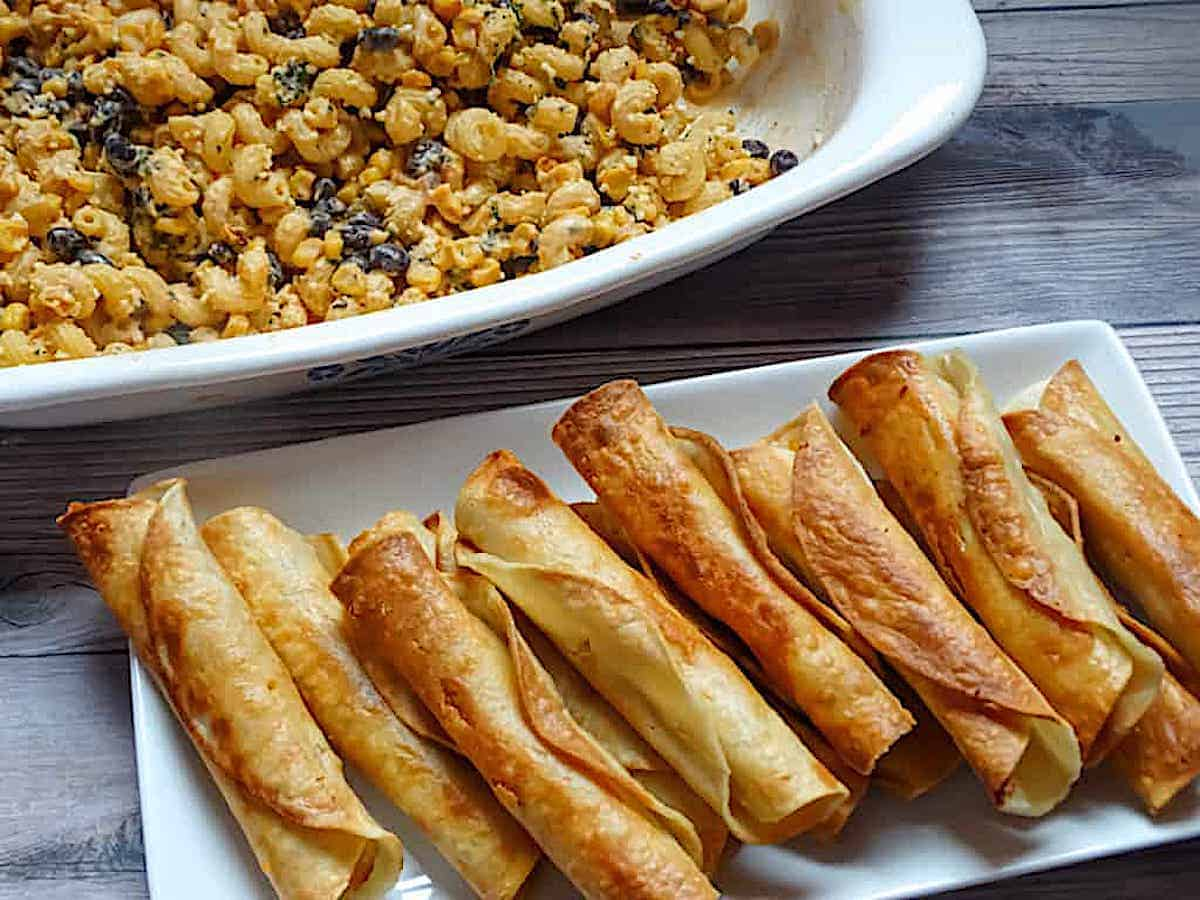 easy pan-fried chicken taquitos on a white plate, served with Mexican street corn pasta salad.