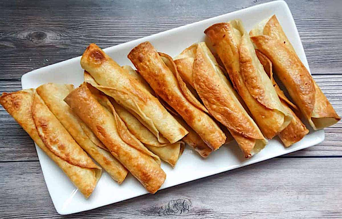 pan-fried chicken taquitos on a white plate and on a wooden background