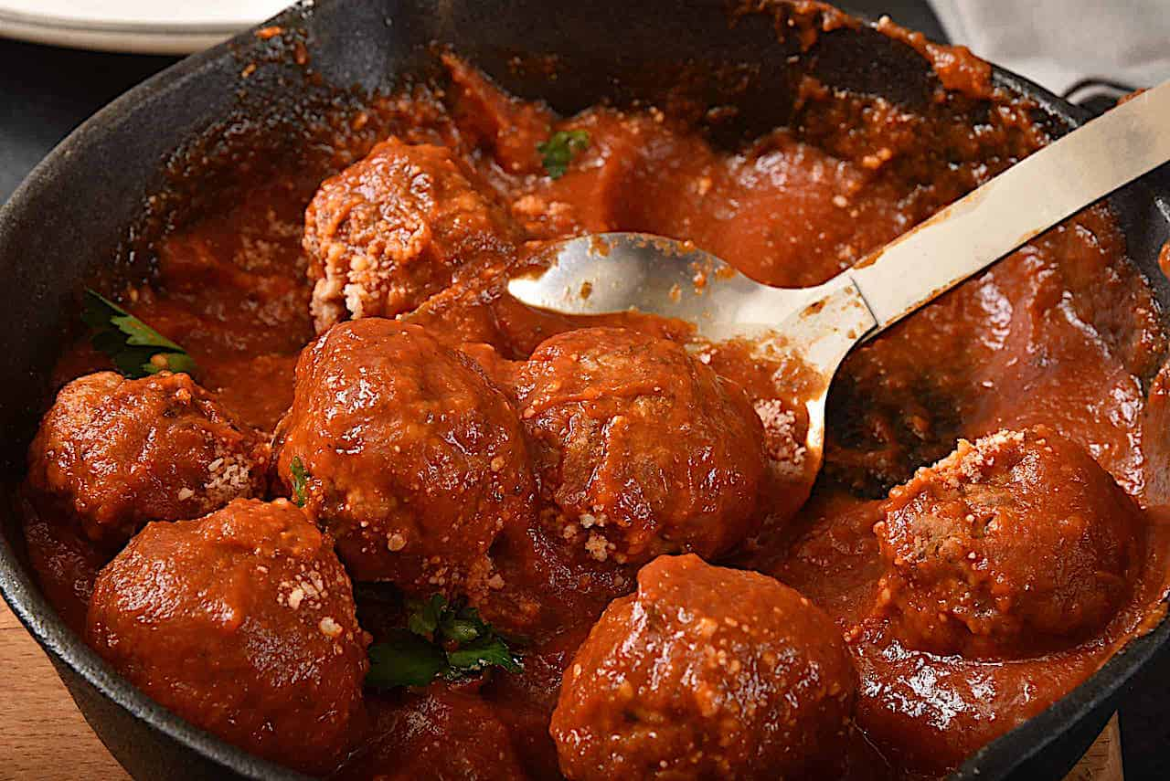 homemade meatballs in a pot of tomato sauce