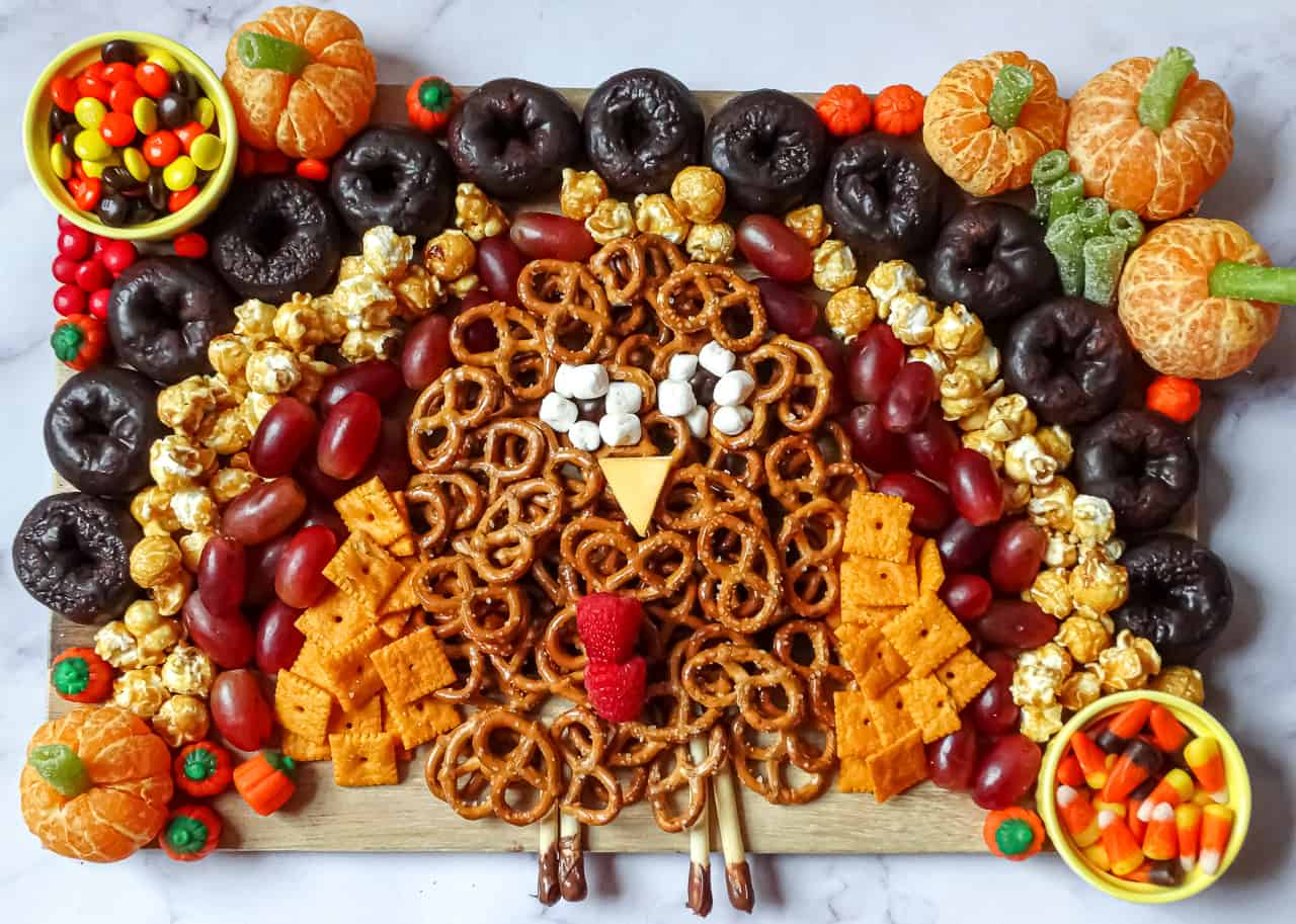 a turkey shaped charcuterie board on a rectangle cutting board, using grapes, crackers, popcorn and donuts
