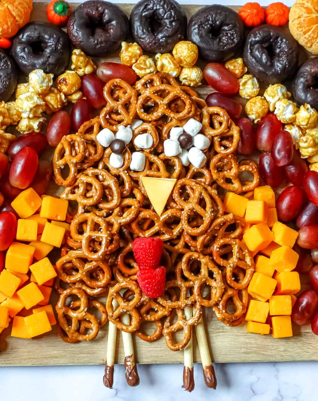 a turkey shaped from pretzels and cheese cubes as a thanksgiving appetizer for kids