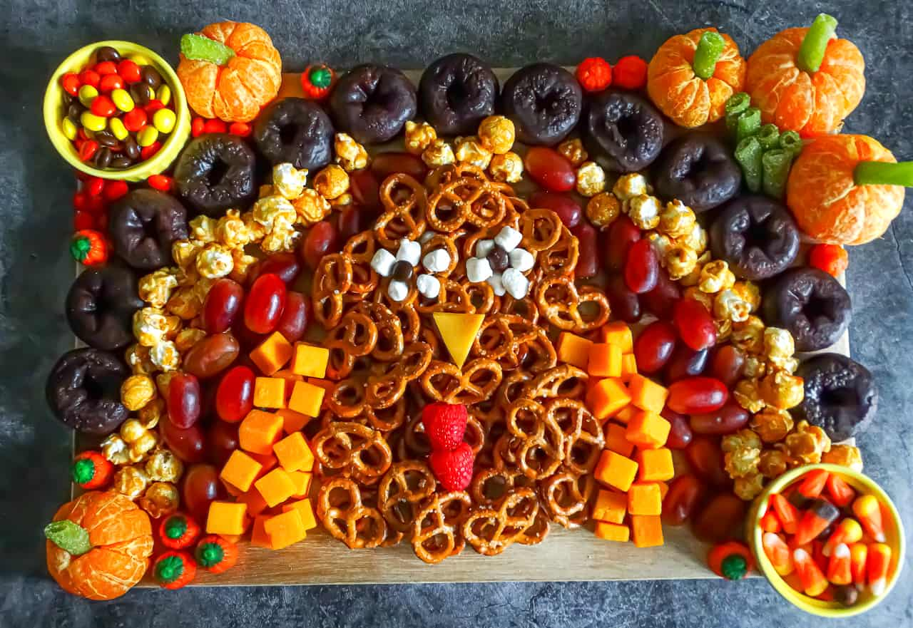 A turkey shaped charcuterie board with pretzels, cheese its, grapes, popcorn, donuts, and candy pumpkins