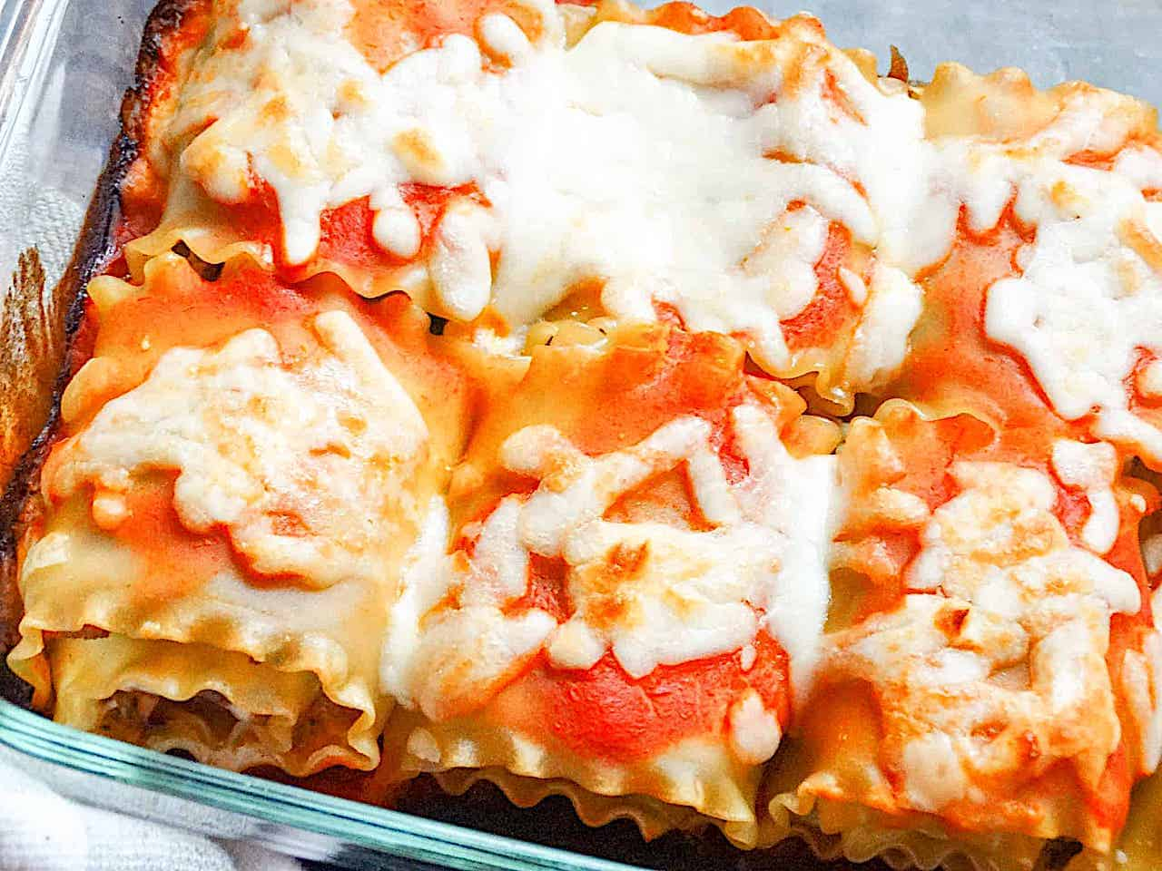 lasagna roll ups topped with mozzarella in a glass pan