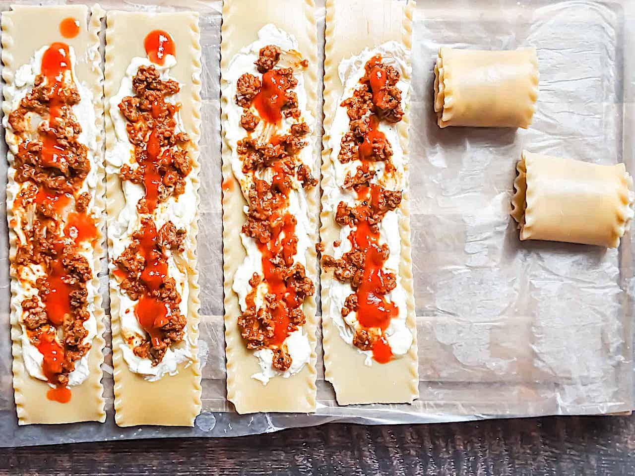 lasagna roll ups with ground beef and sauce on a parchment lined baking sheet