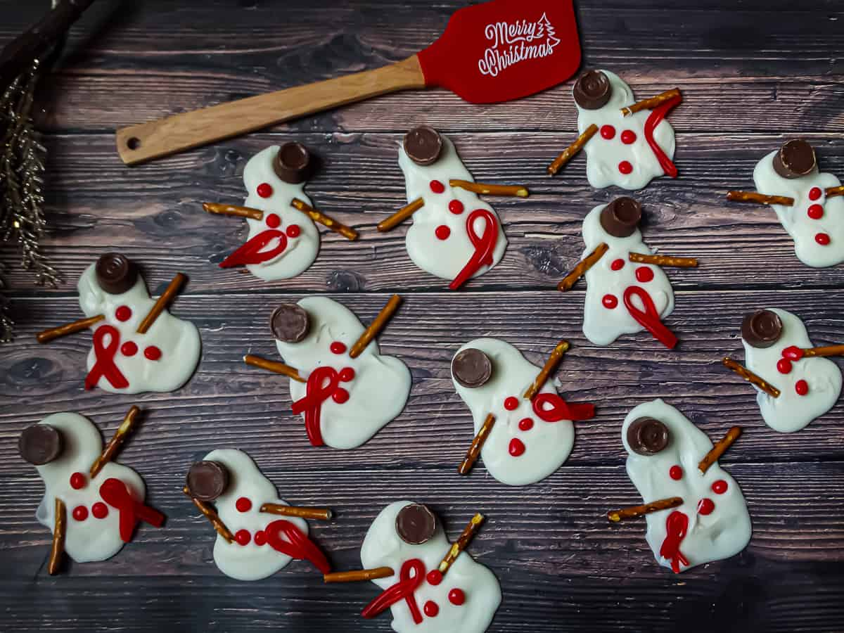 melted almond bark in the shape of snowmen on a wooden background