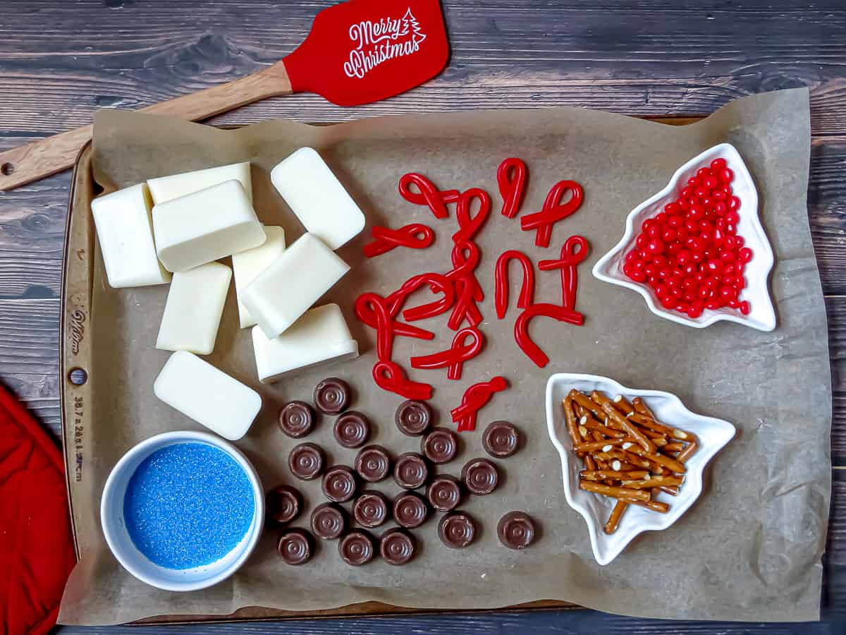cinnamon imperials, twizzlers, pretzel sticks, rolos, blue sprinkles and almond bark cubes on a baking sheet