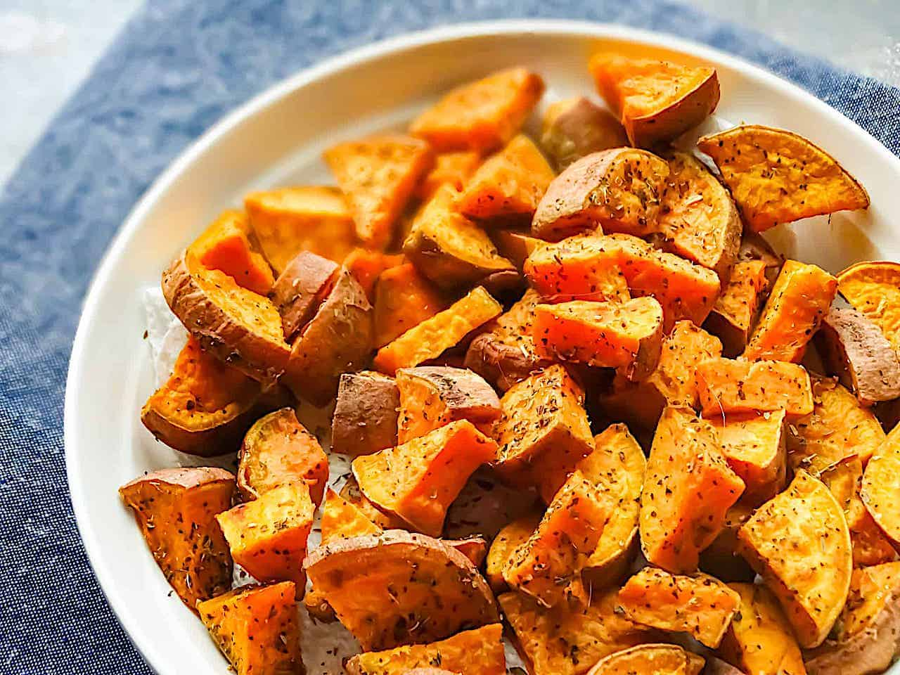 oregano roasted sweet potatoes on a white plate