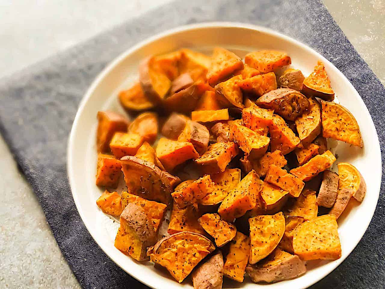 oregano roasted sweet potatoes on a white bowl and blue placemat