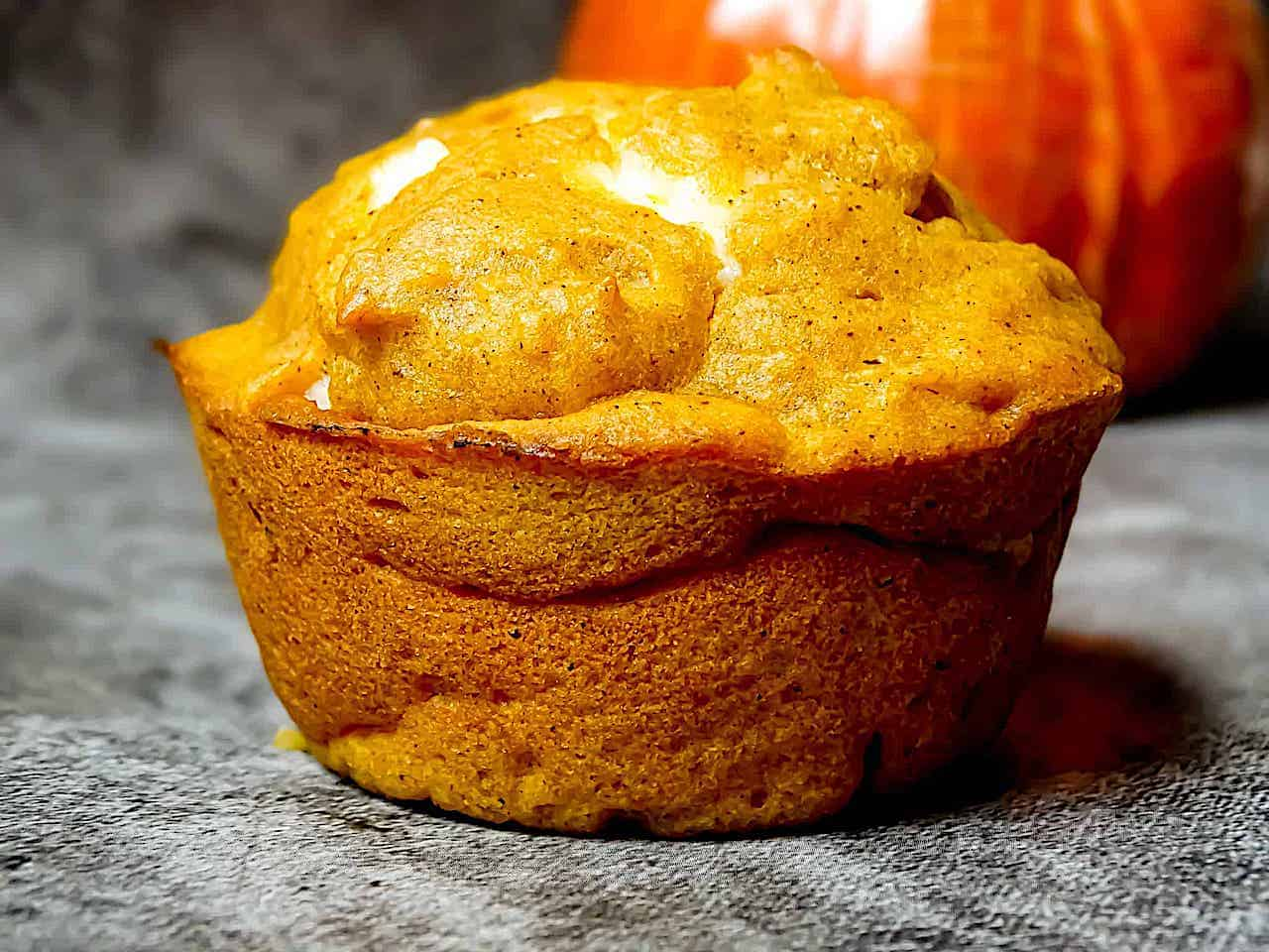 pumpkin cream cheese filled muffin on a gray background
