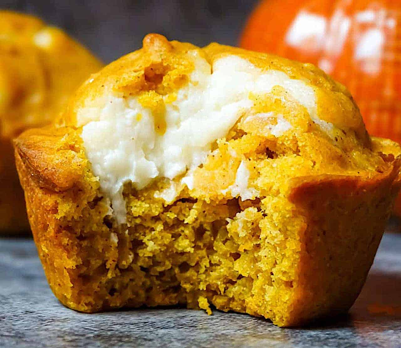 close up of a pumpkin muffin with a bite out to show the cream cheese filling