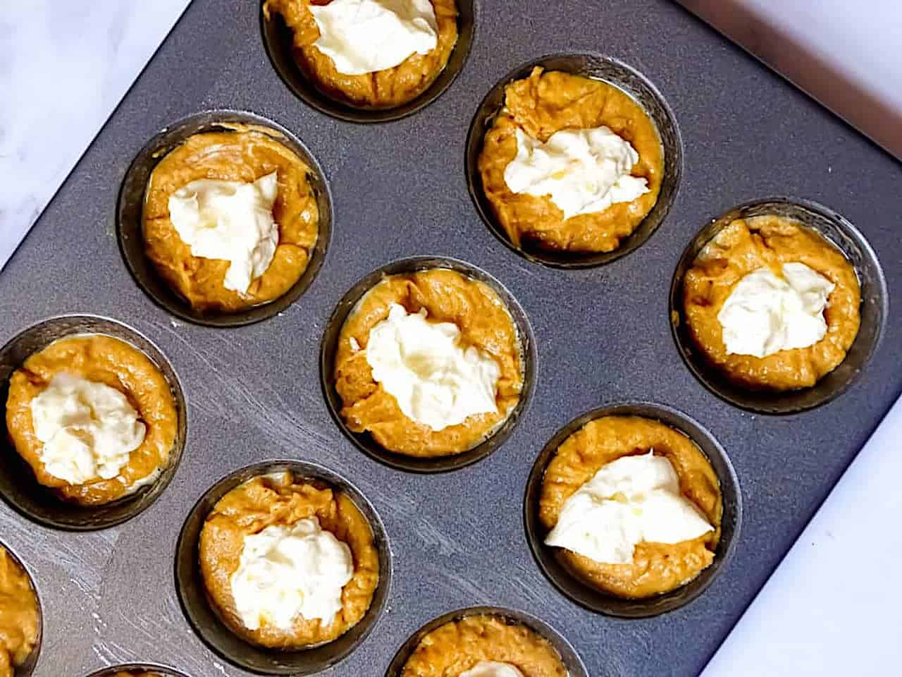 pumpkin muffin batter and cream cheese filling in a muffin tin