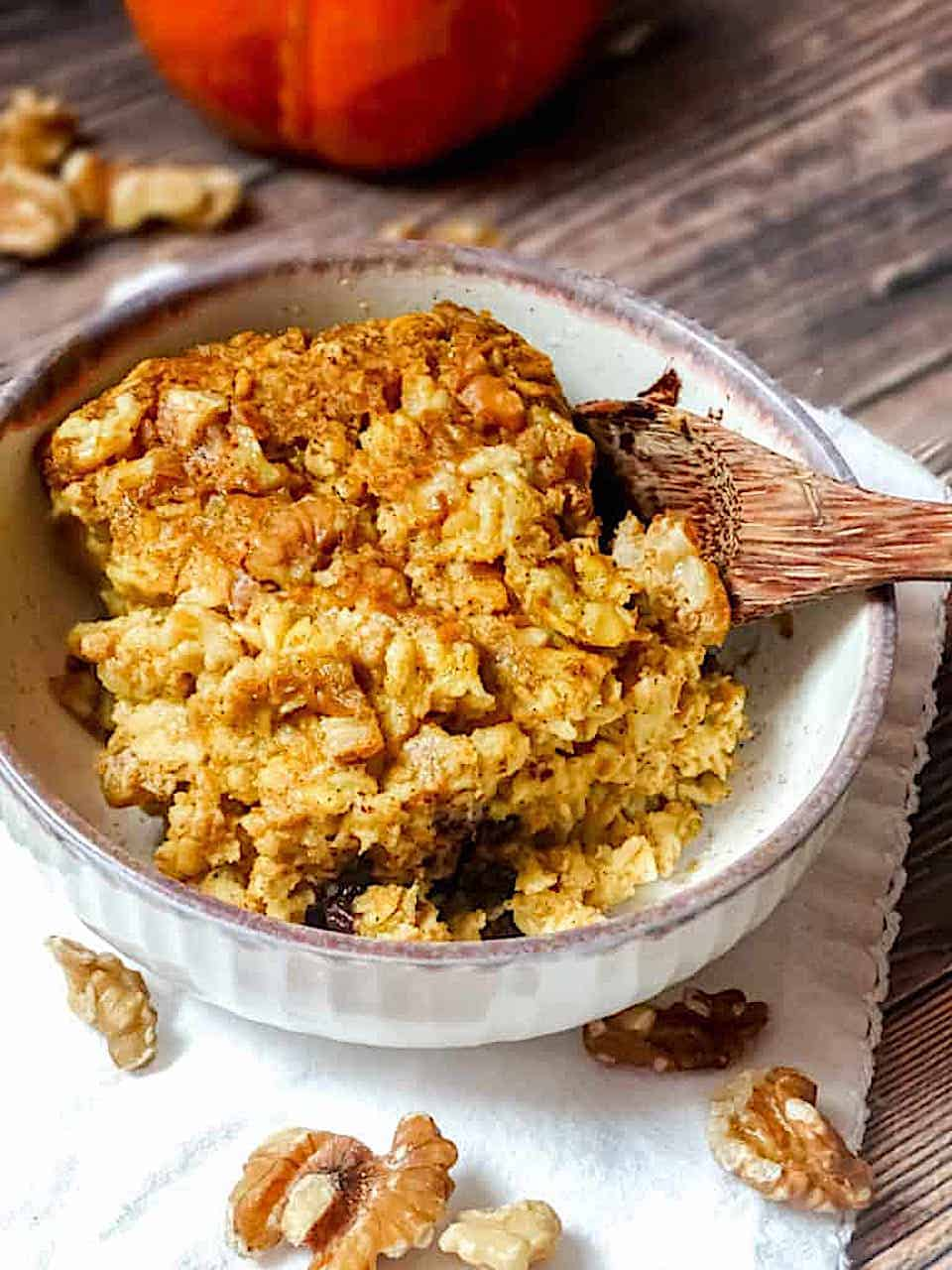 pumpkin baked oatmeal in a white bowl on a dark brown background