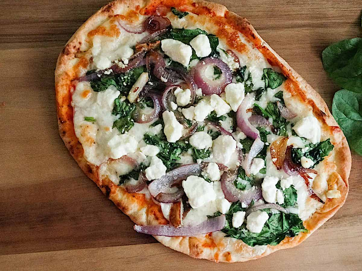 spinach and feta flatbread pizza using na'an on a cutting board