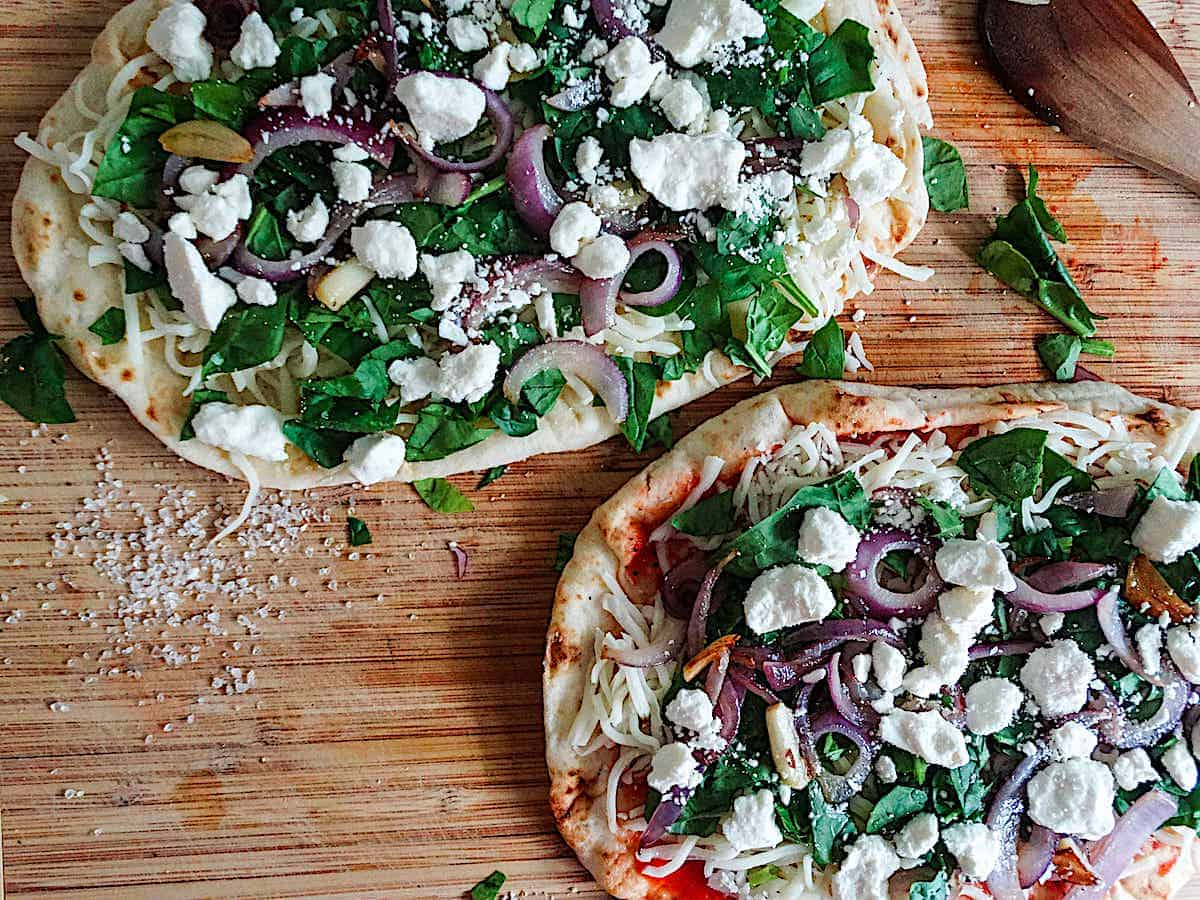 two uncooked spinach and feta flatbreads topped with mozzarella, red onions, and garlic on a cutting boar