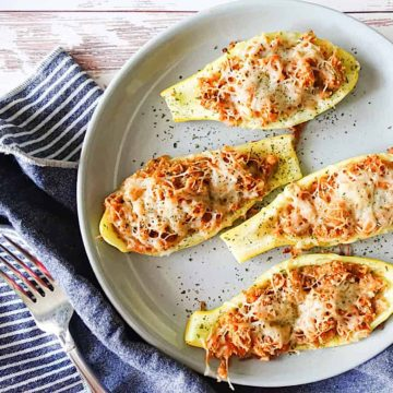 cheesy roasted squash boats on a gray plate