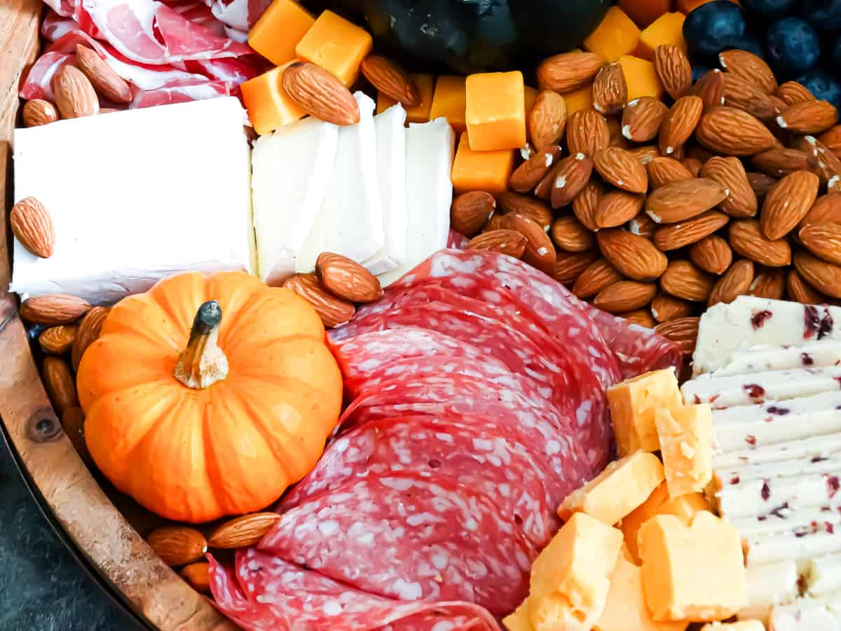 Meats, cheeses, fruits, nuts, and spreads arranged on a circular board intended to be an easy Thanksgiving appetizer