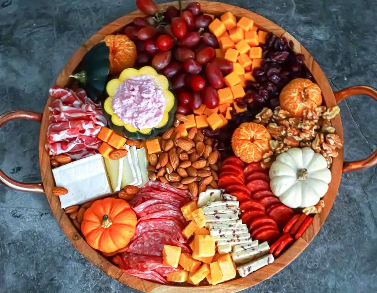 Thanksgiving charcuterie board filled with nuts, meats, cheeses, pumpkins and fruits in vibrat fall colors