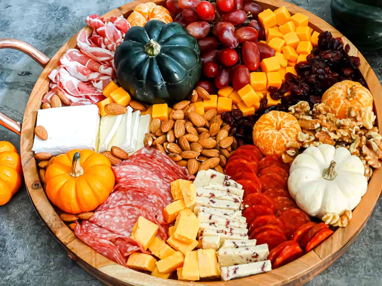 A Thanksgiving charcuterie board filled with nuts, cheese, pumpkins, and grapes