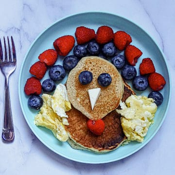 turkey shaped pancakes with strawberry and blueberry feathers, and egg wings