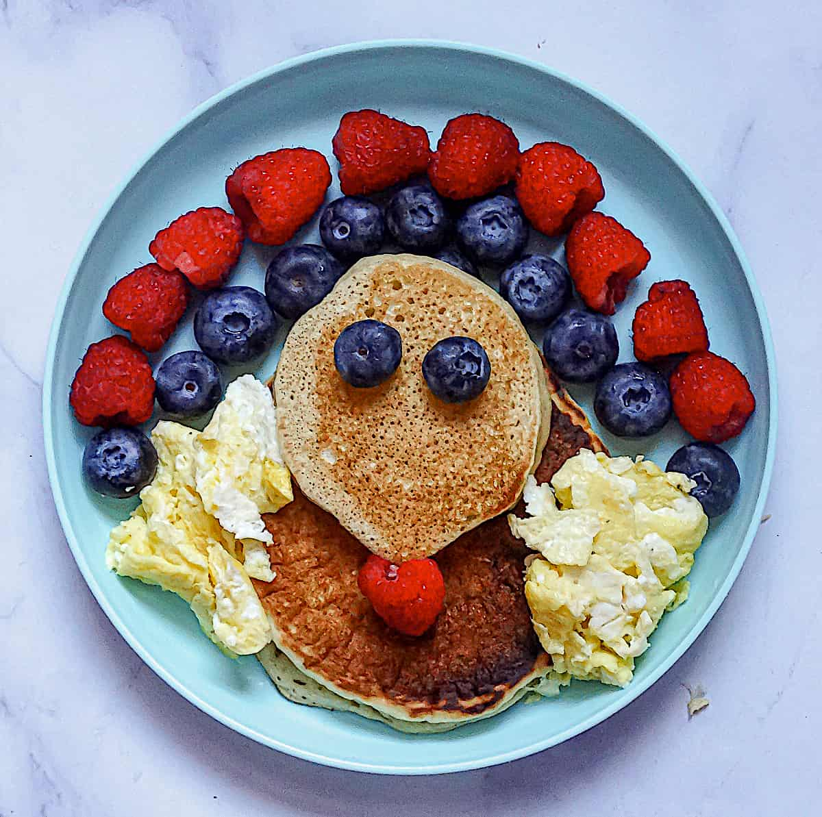 thanksgiving pancakes with 2 pancakes, blueberry eyes and blueberry and raspberry feathers and egg wings