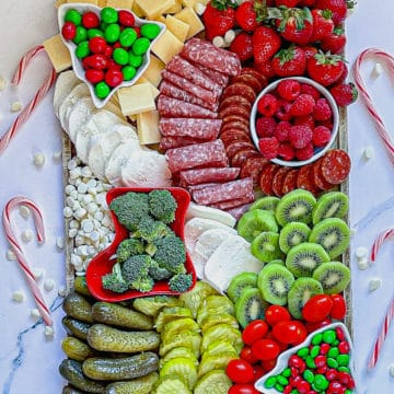 Christmas charcuterie board with red, white, and green fruits, vegetables, meats and cheeses surrounded by candy canes