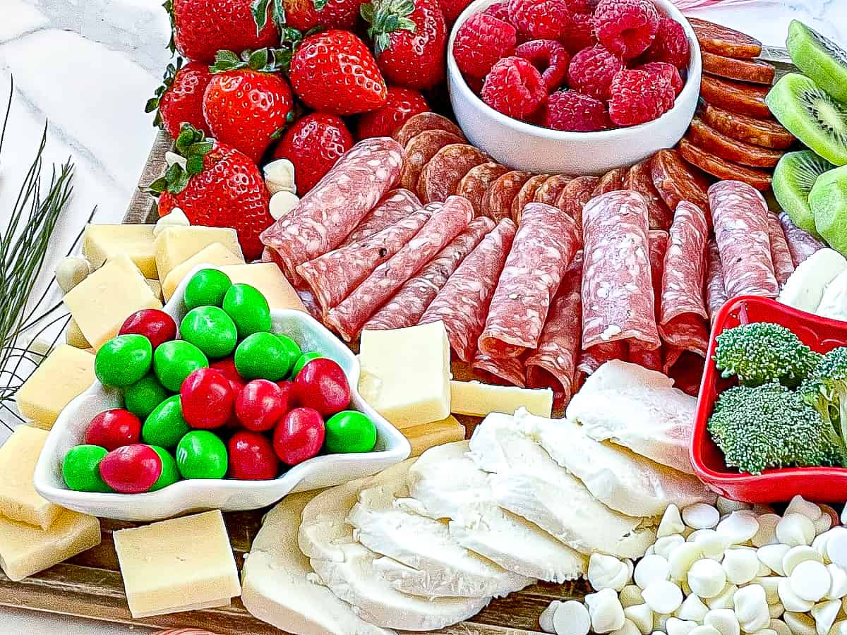 Christmas charcuterie board with red fruit and meat and white cheese