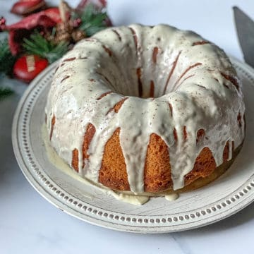 eggnog cake on a white plate, glazed with icing and sprinkled with nutmeg