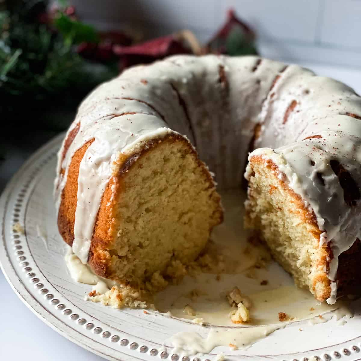 sliced eggnog cake on a white platter surrounded by Christmas decorations