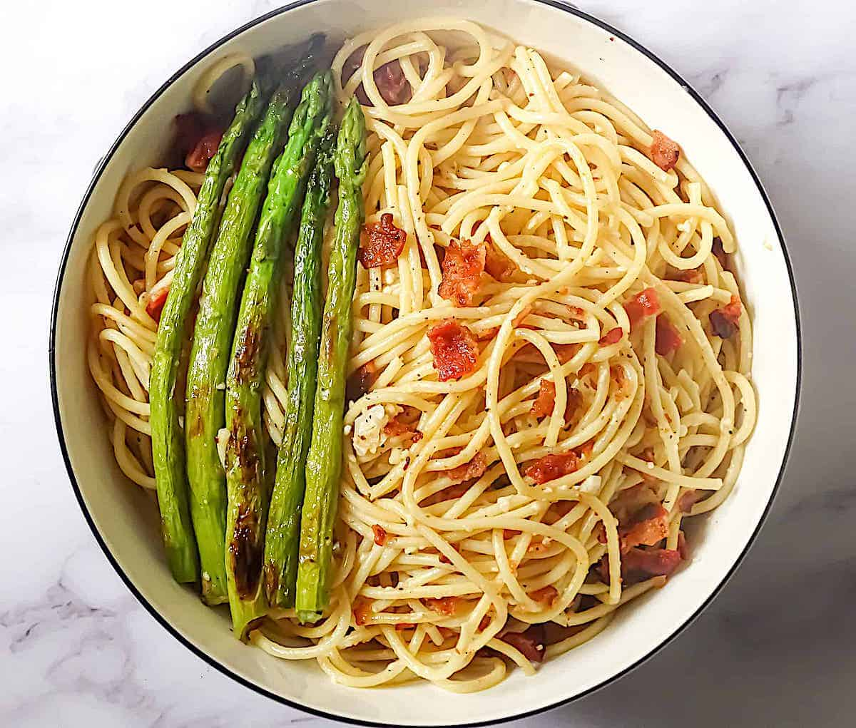 garlic butter pasta with bacon bits and fried asparagus in a white bowl