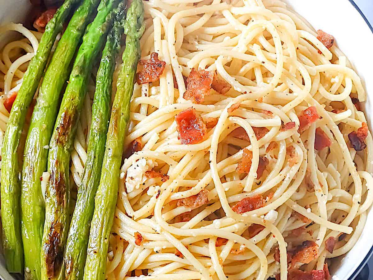 close up of garlic butter pasta and asparagus in a bowl