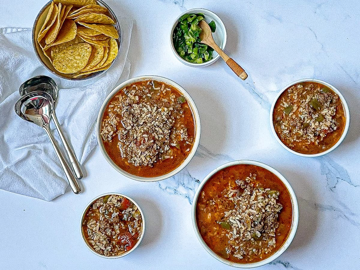 instant pot stuffed pepper soup in 4 bowls topped with chives and served with dipping chips