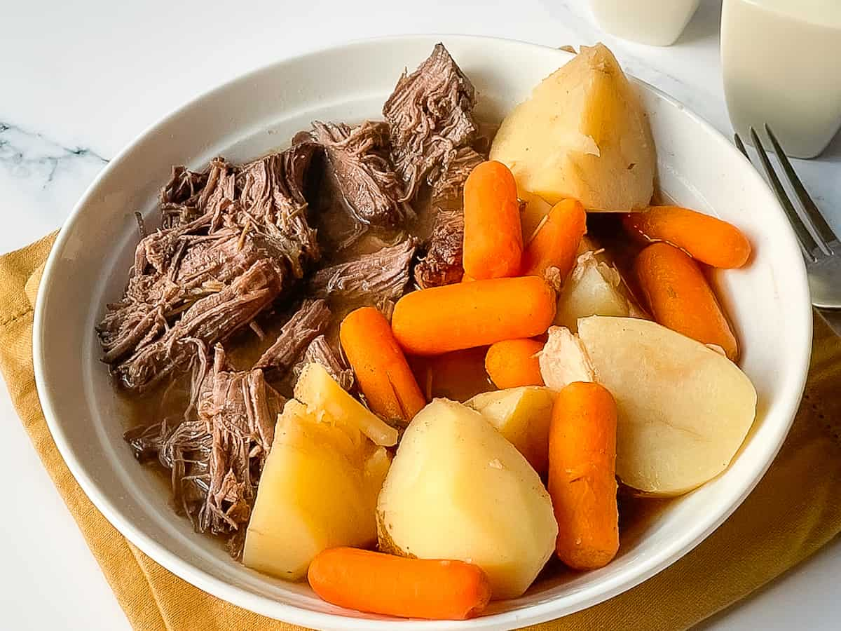 instant pot venison stew with carrots and potatoes in a white serving bowl
