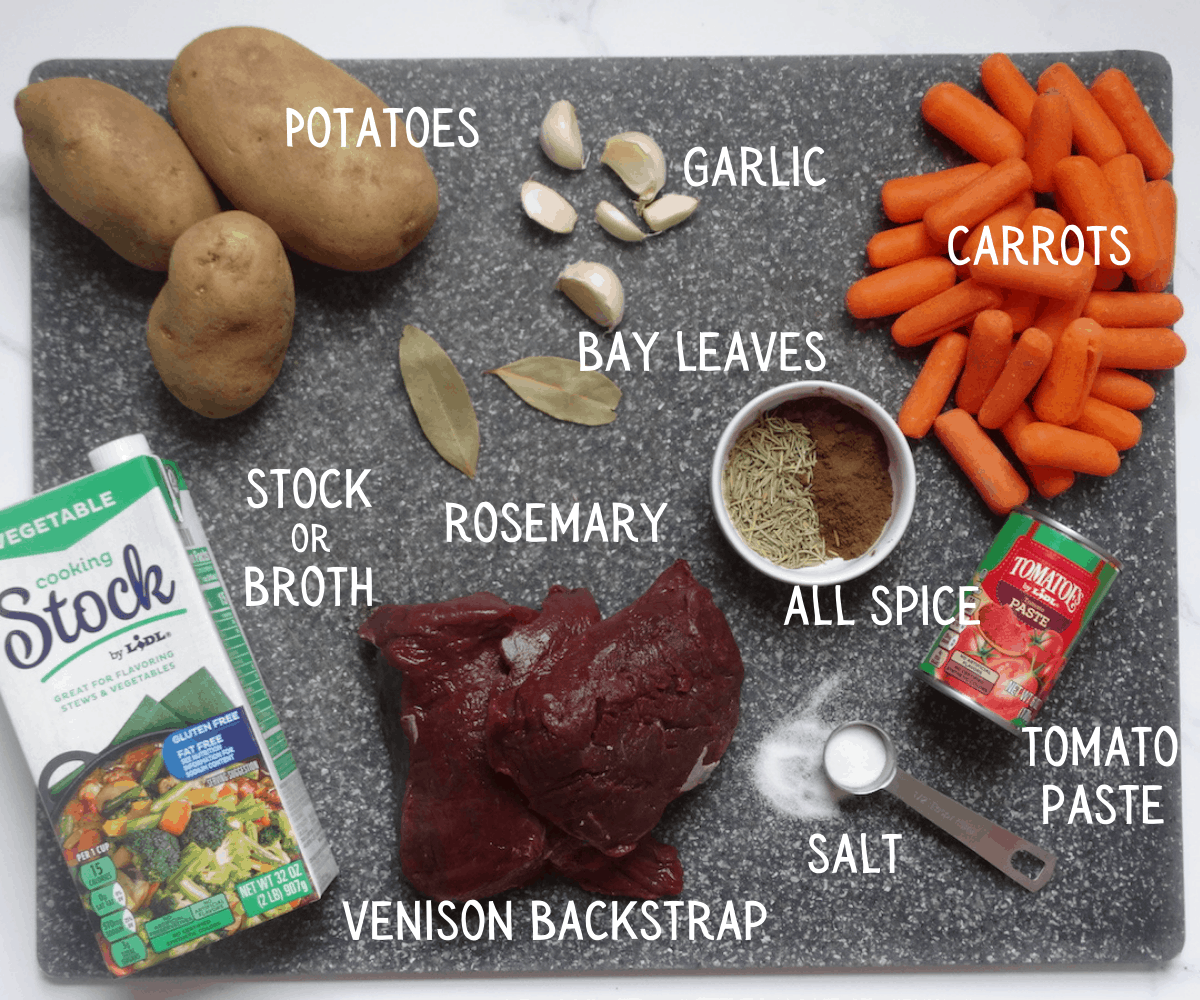 ingredients for venison stew on a gray cutting board and labeled