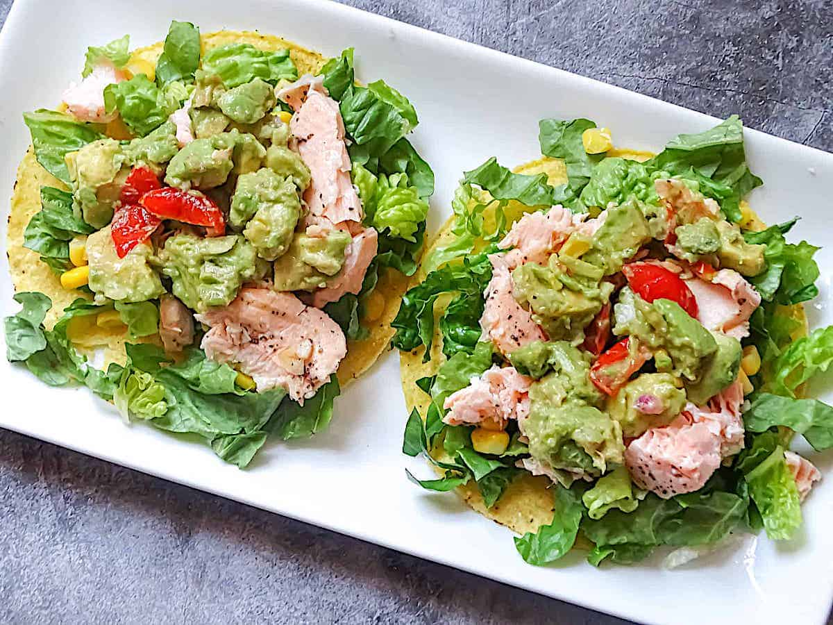 salmon and avocado tostada on a white plate