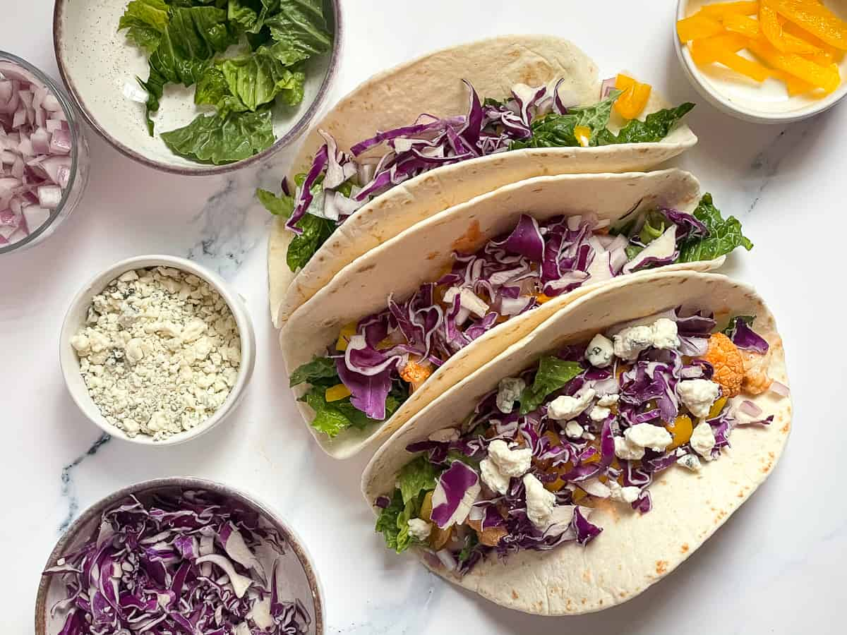 buffalo cauliflower tacos topped with red cabbage and blue cheese on a white background surrounded by fresh vegetables