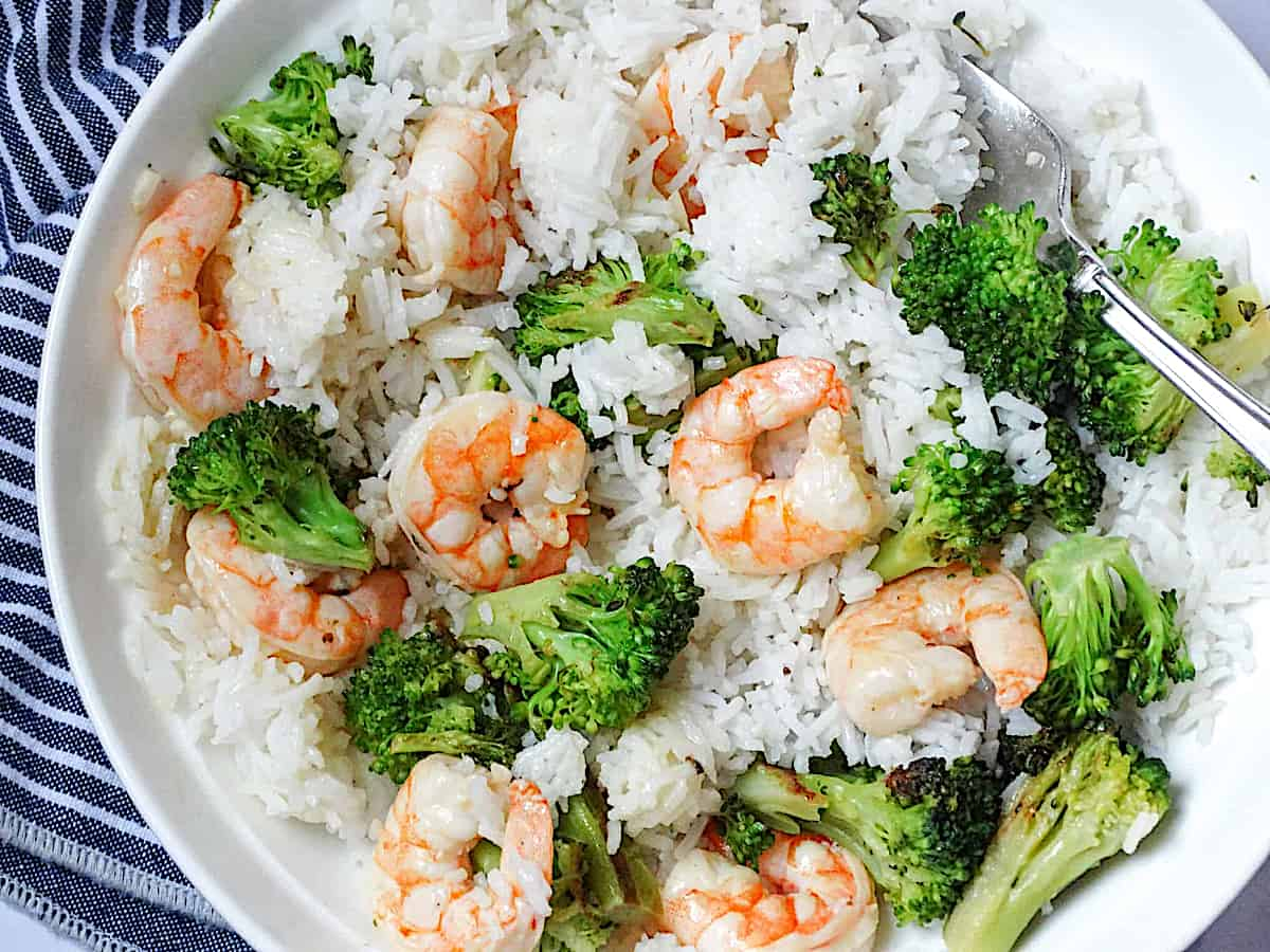 shrimp, rice, and broccoli mixed together on a plate