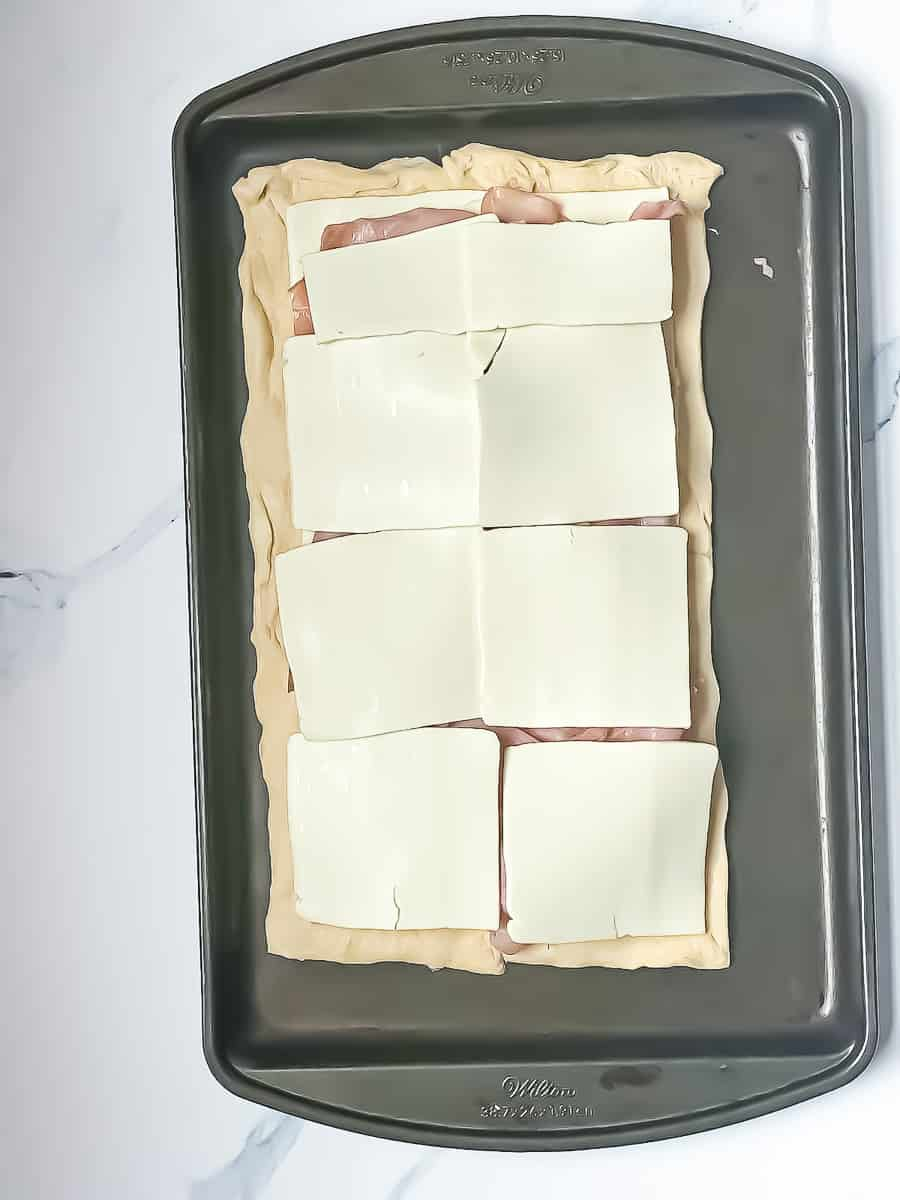 croissant dough, sliced cheese, ham, and sliced cheese layered on a baking sheet