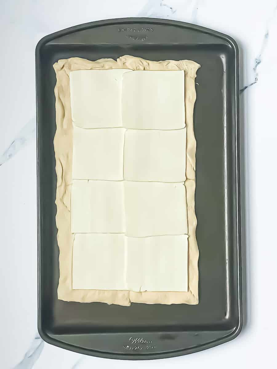 croissant rectangle spread out on a baking sheet topped with sliced cheese