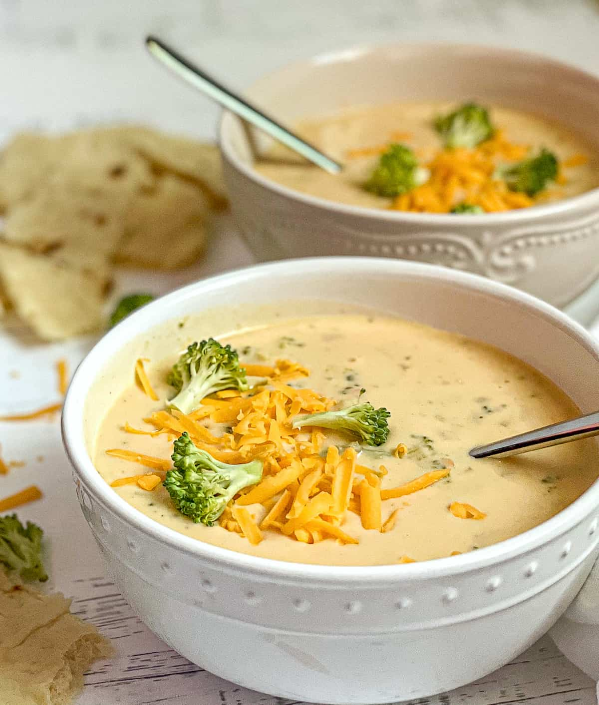 2 bowls of creamy instant pot broccoli cheddar soup, topped with extra broccoli and cheese