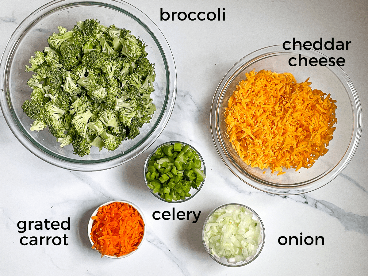 cheddar cheese, broccoli, celery, onion, and carrot on a white background