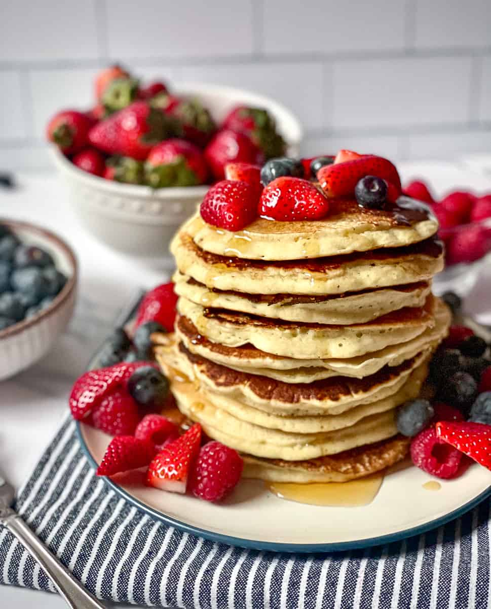 oat milk pancakes in a high stack topped with strawberries, blueberries and syrup